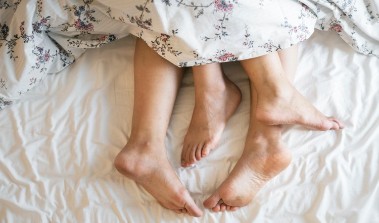 Exercise Hacks: How to be fitter without really trying. Couples barefeet protruding from under duvet cover