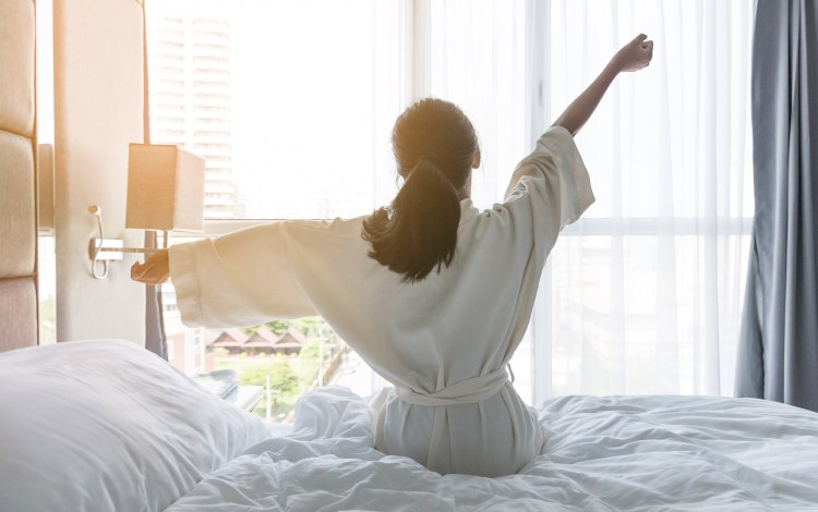 Sleep well: How to win at sleeping! (and why you should want to). How to get a good night's sleep. Image of young woman waking up, stretching out her arms, facing a floor to ceiling window with light pouring in