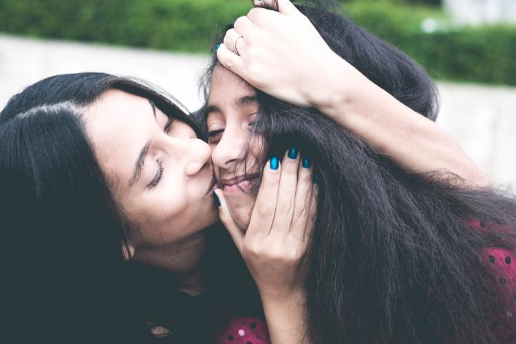 Give the gift of well-being this Mother's Day: Perfect well-being gifts for Mum. Image of mum kissing daughter on the face