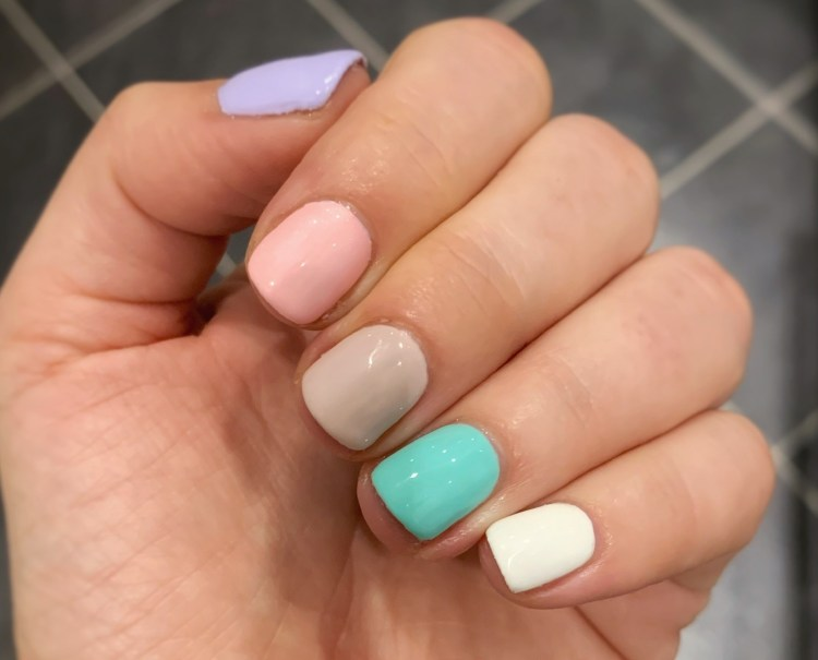 Here comes the sun:  the easy ways to get yourself summer ready.  Image of hand displaying pretty bright nail colours for summer