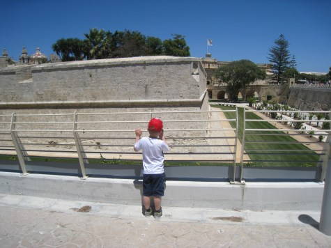 Happy Travels: Where you absolutely should go in Malta. Image of little boy standing at the railings about to enter Mdina