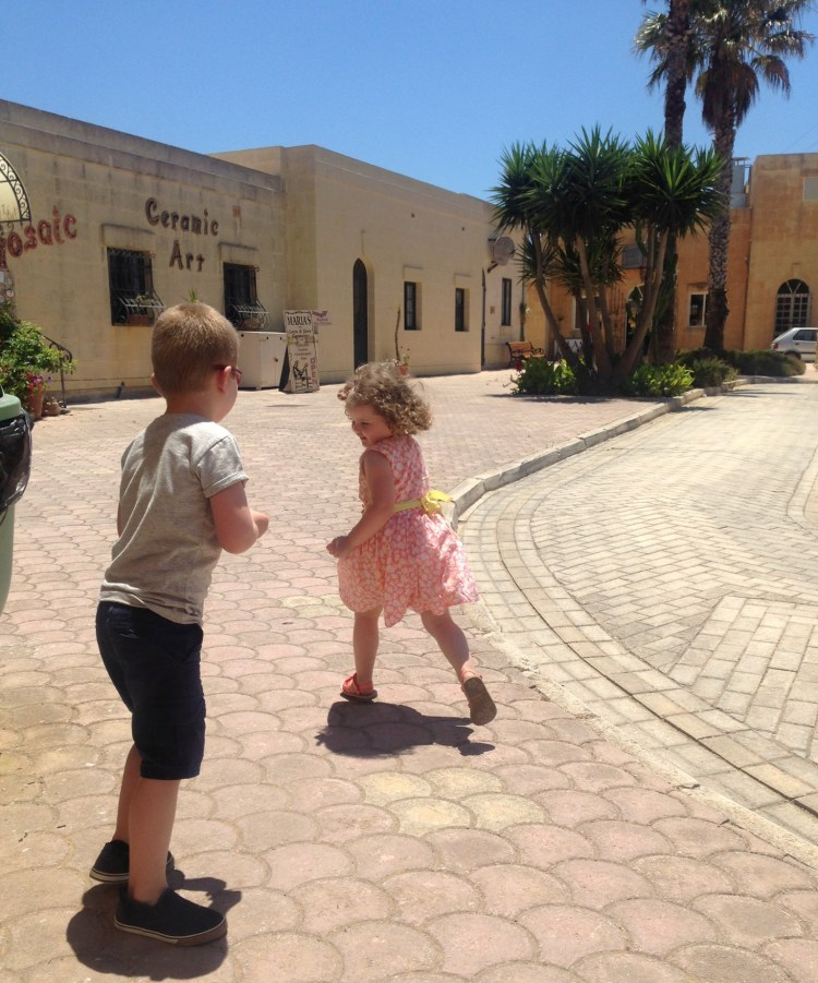 Happy Travels: Where you absolutely should go in Malta. Image of a young girl and boy running around and playing at Ta'Dbiegi craft village Gozo