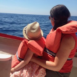 Happy Travels: Where you absolutely should go in Malta. Image of woman and young girl on a boat at Dwejra Bay Gozo