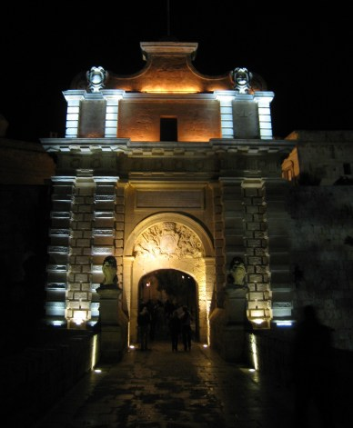 Happy Travels: Where you absolutely should go in Malta. Image of entrance to Mdina at night