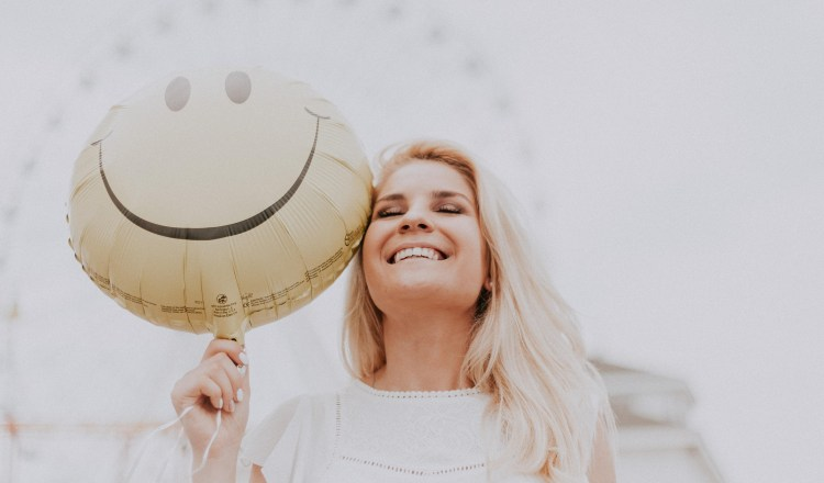 A Thousand Thanks: Why practising gratitude increases your happiness. Image of smiling woman holding happy emoji balloon