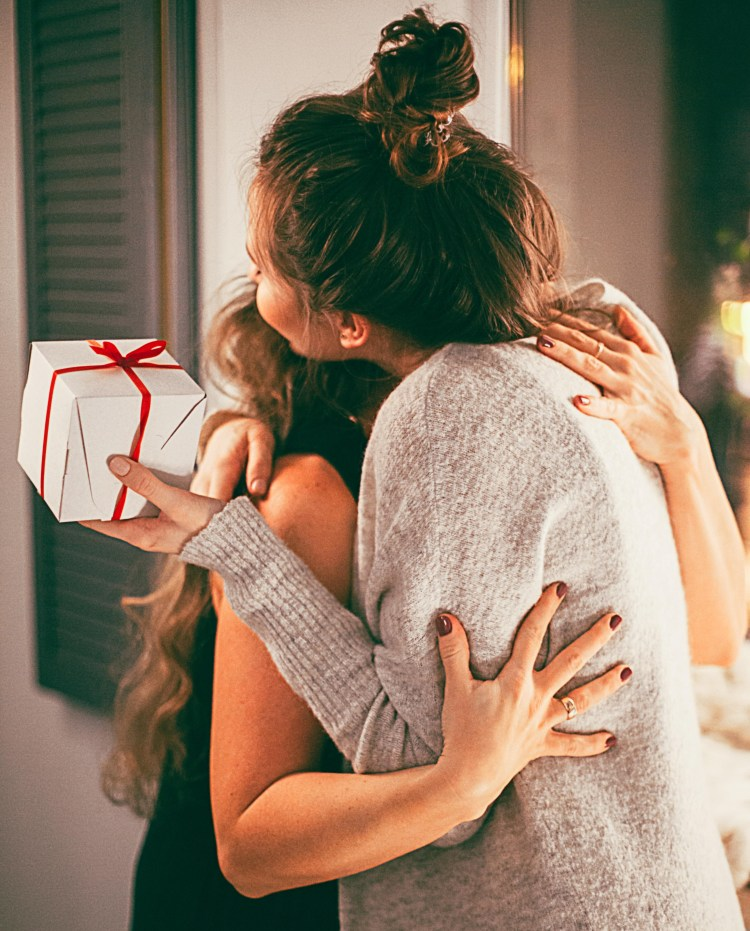 A Thousand Thanks: Why practising gratitude increases your happiness. Image of 2 women embracing and 1 is holing a gift box in her hand