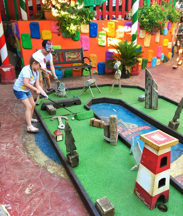 Fun things to do in Malta with Kids.  Playing crazy golf at Popeye Village