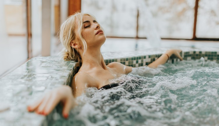 And relax... All the benefits of a spa day and how to make the most of them. Image of woman relaxing in the whirlpool bathtub