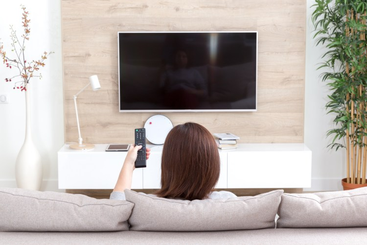 How to stop catastrophizing, avoid triggers. Image of Young woman watching TV in living room, back view