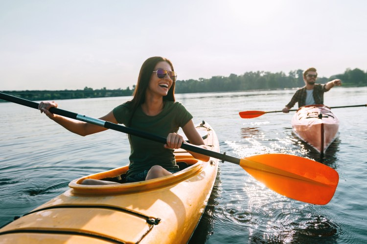 Let's give it a go: becoming more open to new experiences. Image of couple kayaking together on a lake and smiling having fun