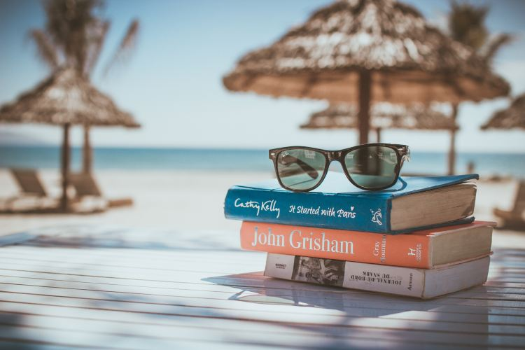 happy on holiday. Image of books on a table with a pair of sunglasses resting on top on a tropical beach