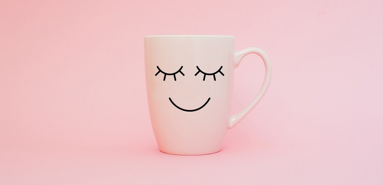 The benefits of smiling. Everything you need to know (but didn't realise) about smiling. Image of a white mug with a smiling face drawn on against a pink background