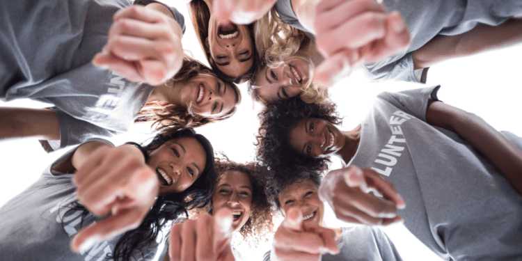 Feeling good for doing good: Why volunteering benefits everyone. Image of a group of females wearing grey t-shirts saying volunteer, smiling and pointing at the camera