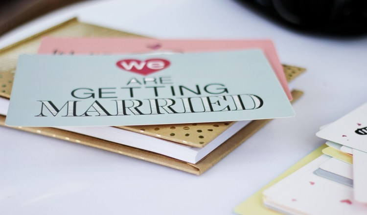 4 Tips to reduce wedding planning stress. Image of wedding stationary with the words we are getting married on one of the cards