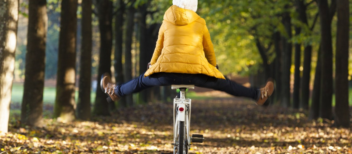 Happy girl riding a bicycle at the park in the Autumn