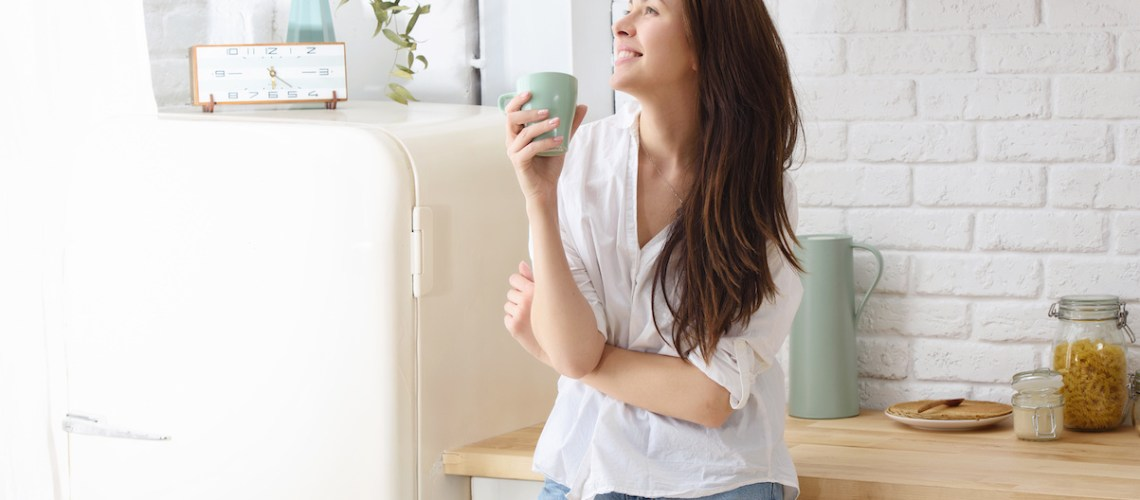 5 Ways to build self-worth. A contented woman stands happily in her kitchen drinking from a mug