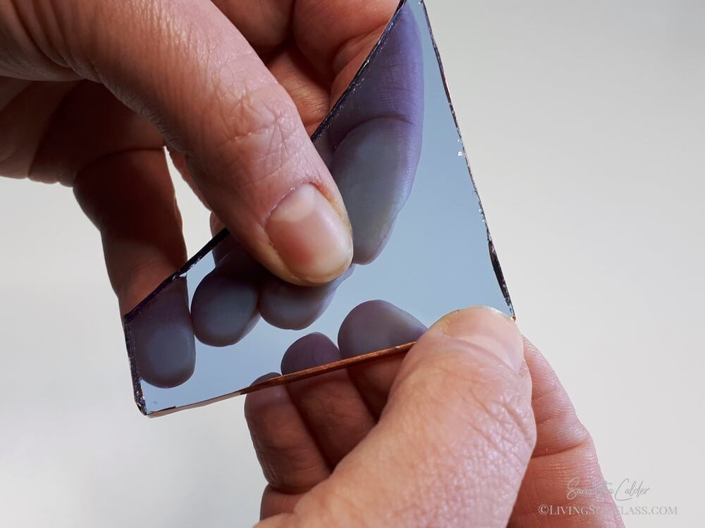 fingers crimp the edges of the copper foil onto the glass