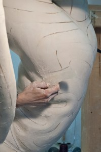 Refining plaster torso.