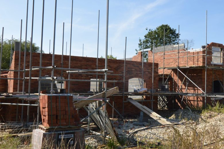 Stowe End house is an Age-friendly house in construction. This image shows the site with a partially constructed house, surrounded by scaffolding.