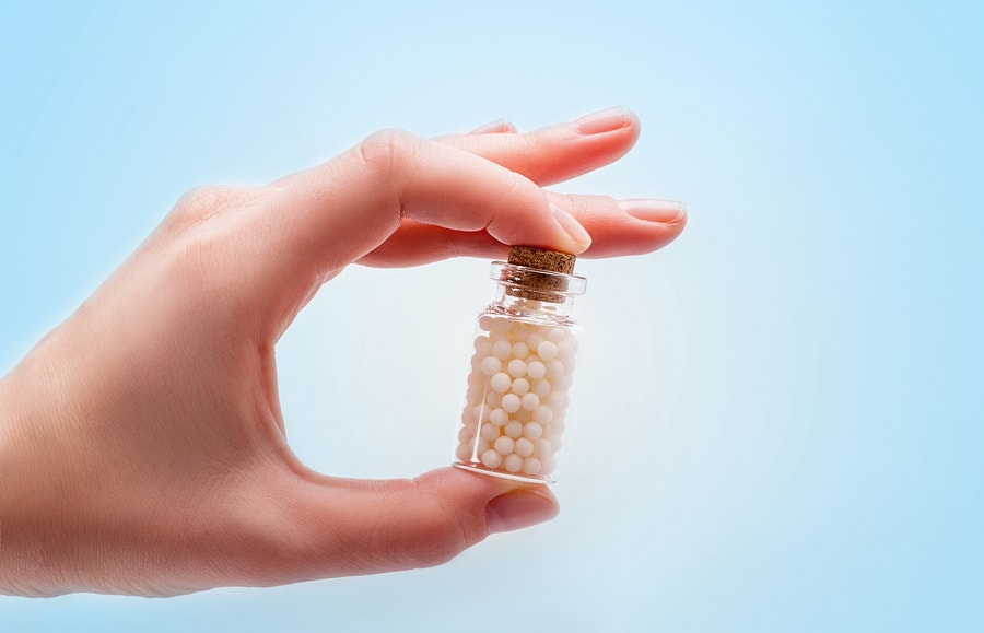 Woman hands holding a bottle with homeopathic pills on white background
