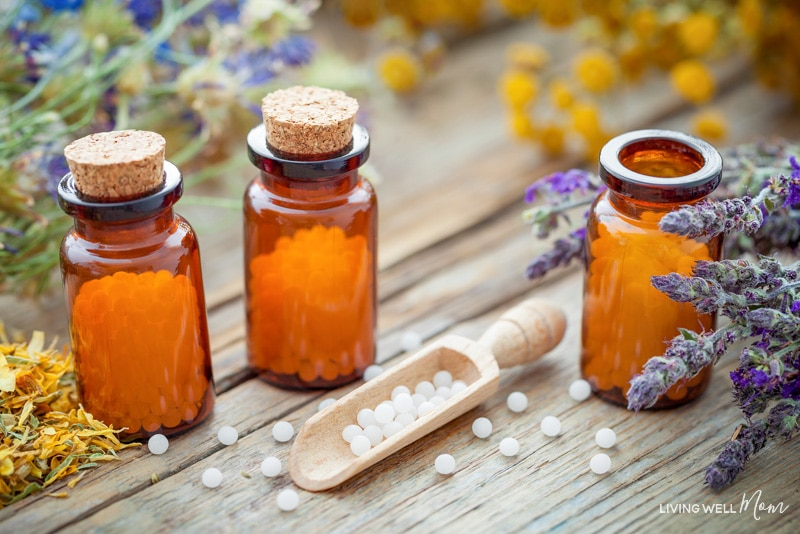 Bottles of homeopathic globules and healing herbs. Homeopathy medicine concept.