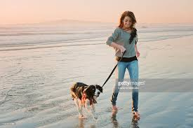 girl runnning dog on beach