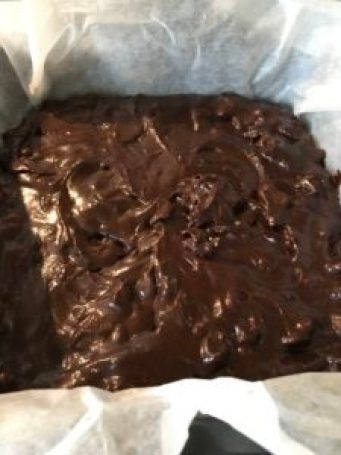 Chocolate brownie mixture in a baking tray.