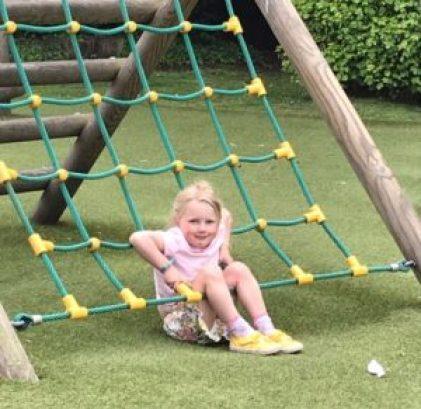 Emmeline, sitting on climbing netting in the park