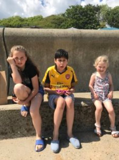 Jude, Elsa and Emmeline sitting on a wall at the beach