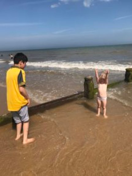 Jude and Emmeline paddling in the sea