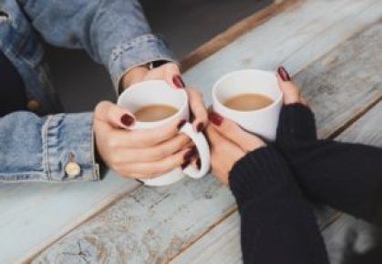 two pairs of hands holding white mugs.