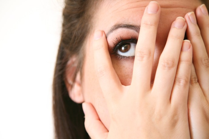 worried-or-embarrassed-woman-covering-face-peeking-10056970