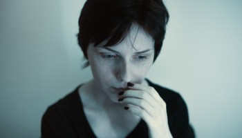 pensive-woman-hand-on-mouth