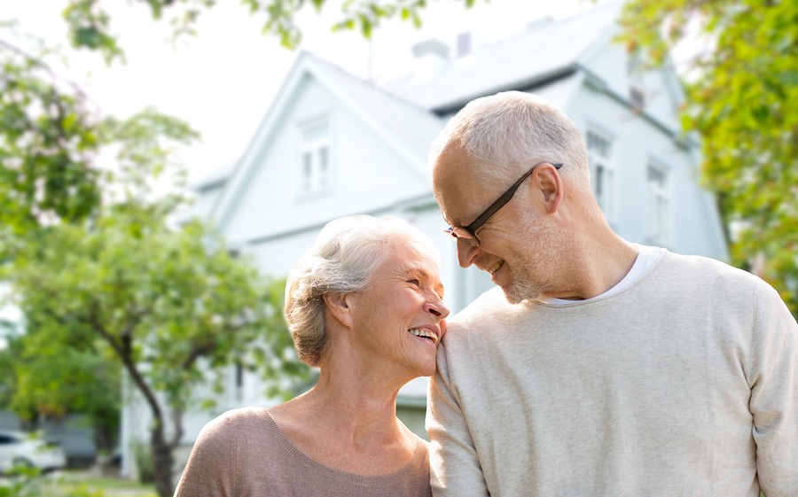 family, age, home, real estate and people concept - happy senior couple hugging over living house background