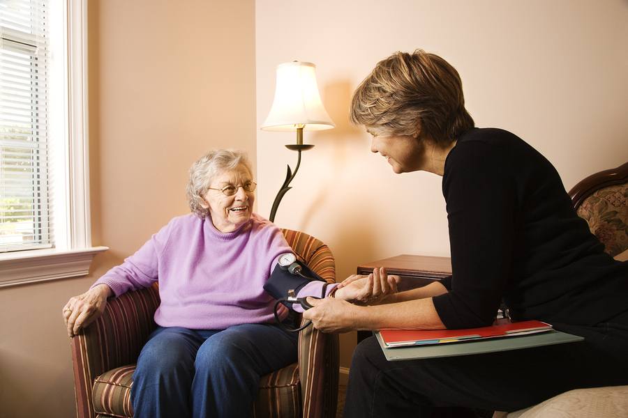 Nurse checks an elderly woman's blood pressure in an assisted living home. Horizontal shot.