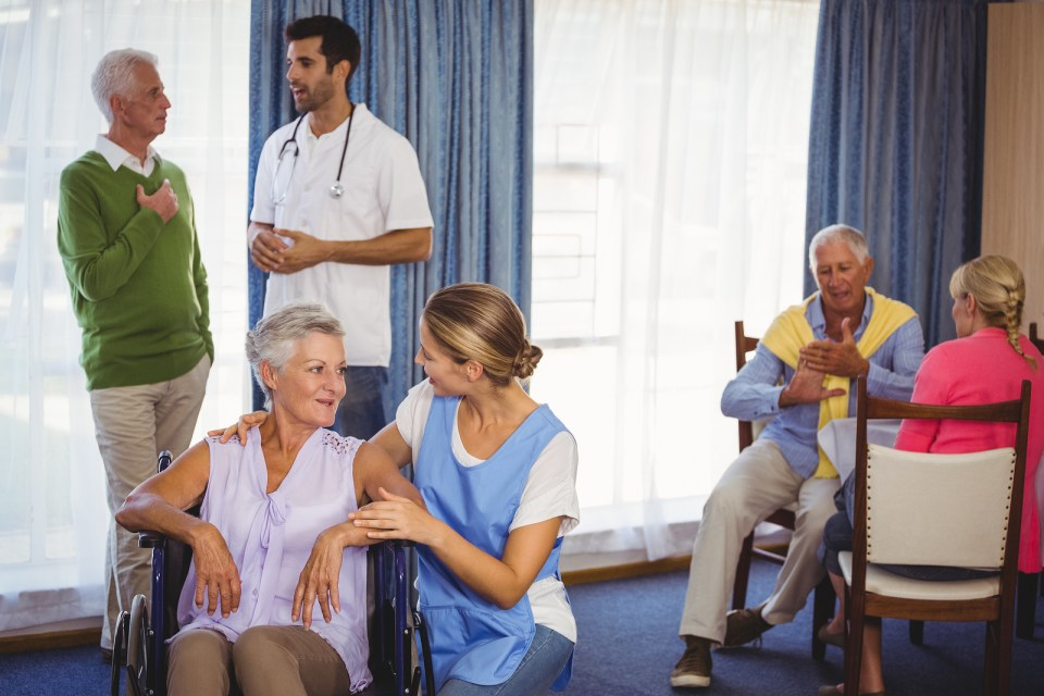 Nurses having discussions with seniors patients in retirement house