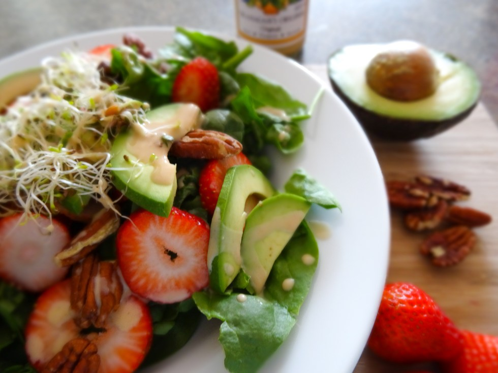 green and red spinach salad with avocado, pecans, sprouts, strawberries and spinach on white and wood
