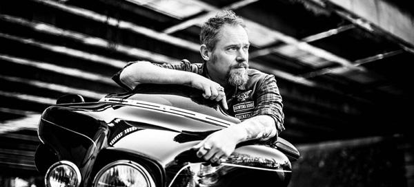Photo en noir et blanc de l'auteur Henri Loevenbruck assis sur sa moto