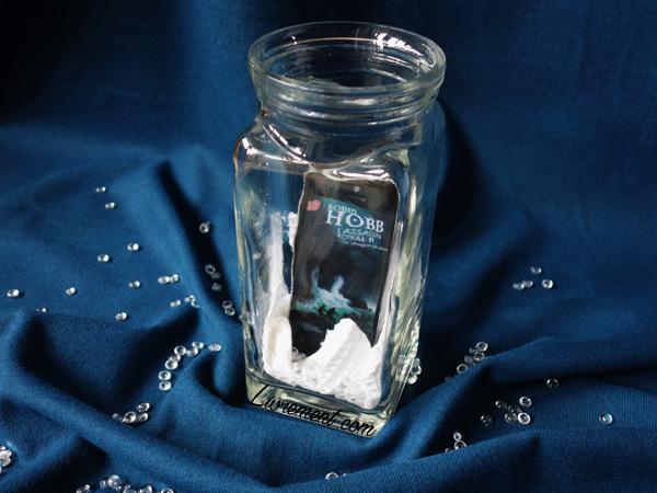 """Mise en scène du livre """"Le dragon des glaces"""" de Robin Hobb : livre mis dans un contenant en verre, avec des perles transparentes, avec un tissu bleu"""