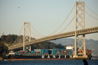 A container ship traveling under the Bay Bridge in San Francisco.