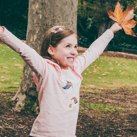 Fun Portrait of a child holding Autumn leaves at Fitzroy Gardens in Melbourne, Australia