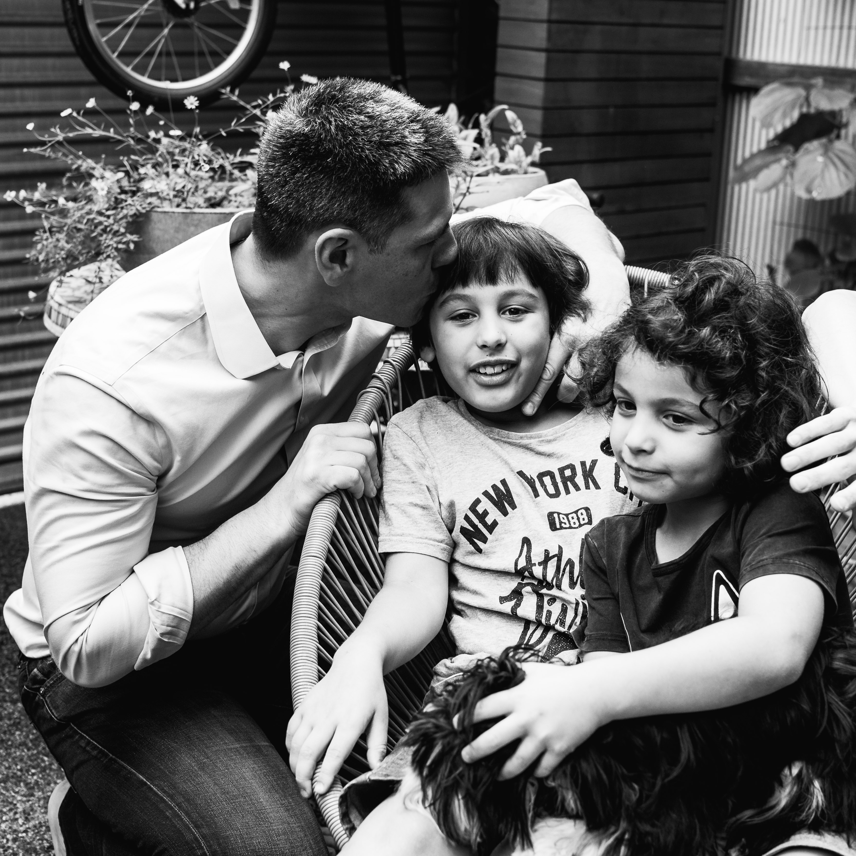 photograph of a father kissing his oldest son in their backyard in Carlton North, Melbourne, Australia