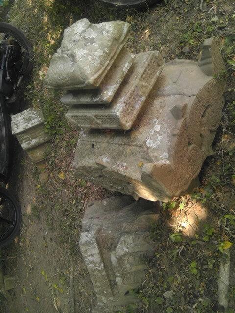 Bagian atas batu nisan yang telah terpisah dari badannya yang berbentuk bulat