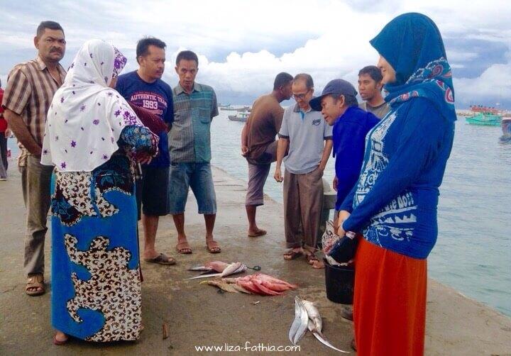 Para pembeli dan penjual sedang tawar menawar harga ikan. Ikan-ikan tersebut baru saja didaratkan oleh para nelayan di dermaga PPI Ujung Serangga Susoh