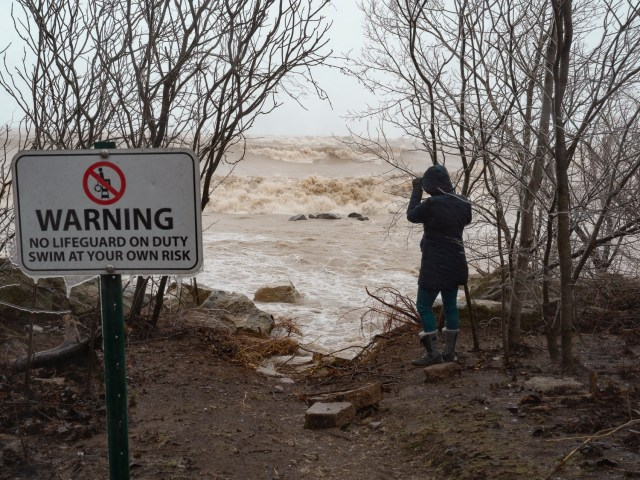 Liz stands on the shores of Lake Michigan and observes rough waves