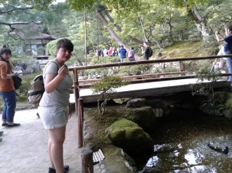 People try tossing coins on the little rock in the pond. Lizzie failed with her monopoly money ¥1