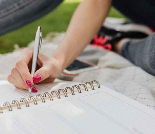crop female noting down daily plans in notebook in park