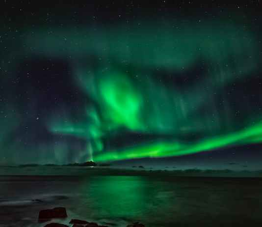 northern lights in starry sky over sea