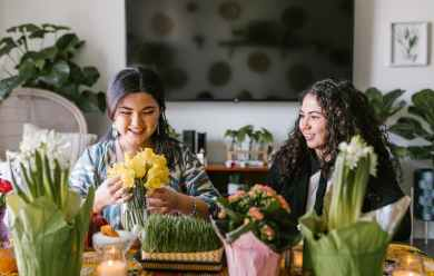 two women sitting by the table with flowers