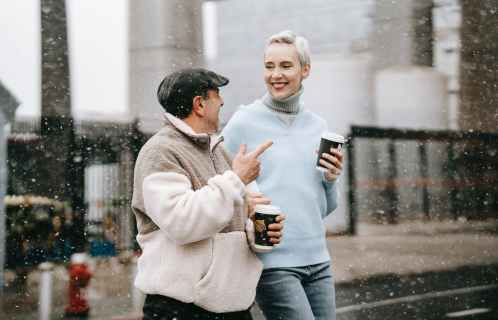 smiling couple talking to each other while having coffee